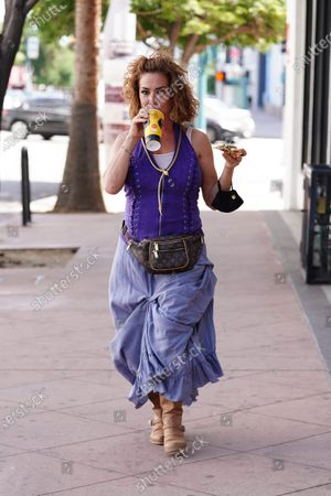 Stock Photo of Claudia Wells eats pizza while on a walk