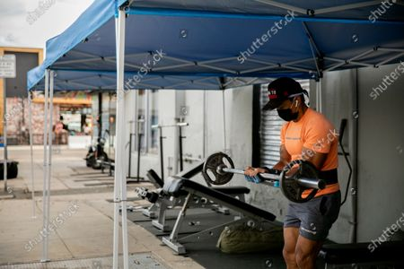 Garry Julian works out at Last Real Gym in the North Park neighborhood on Thursday, Aug. 13, 2020 in San Diego, CA. With gyms ordered closed, the fitness center moved their operations outdoors. (Sam Hodgson / The San Diego Union-Tribune)