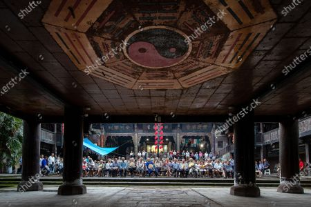 """Stock Picture of On the evening of August 9, 2020, At Qingyuan Palace in Jiangjin, Chongqing, The classical Sichuan opera of China was inherited and the quyi culture was deeply loved. Actors and actresses braved the scorching 38c summer heat to perform Sichuan opera for the enjoyment of rural people. Annual chongqing municipal intangible cultural heritage radically miyagawa main temple fair culture festival kicked off, according to """"metro local dynasty temples"""" records, """"radical palace temple fair"""" began in the Ming dynasty, dating back more than 500 years, including nine will, qing jiao will, sichuan and the main temple fair, light pole, respectively, in the day of the first lunar month, march, June, September, notably the """"sichuan main temple fair"""" is the most grand grand. Every year, half a month before Li Bing's birthday, people from all over the world flock to Qingyuan Palace one after another to worship and remember Li Bing, the """"Lord of wantianchuan"""". Hang red color, kill pig slaughter sheep push bean flower, sing opera parade very lively, before and after will attract tens of thousands of people around to watch and participate. The main assembly of Sichuan """"worship folk custom activities, in order to express the feeling of missing Li Bing, pray for good weather, good grain and abundant harvest. During this period, there will also be a large-scale Lantern Festival and folk drama performances. This important custom of the people in western Chongqing, southern Sichuan and northern Guizhou has been prevalent among the people and has become an important traditional folk activity affecting western Chongqing, southern Sichuan and northern Guizhou. During the temple fair, nearly 100,000 tourists come to pray for the blessing ceremony, known as the folk song said: """"When the meeting, thousands of people come, ten million people go, half jiangjin, half hejiang, noisy, incense constantly""""."""