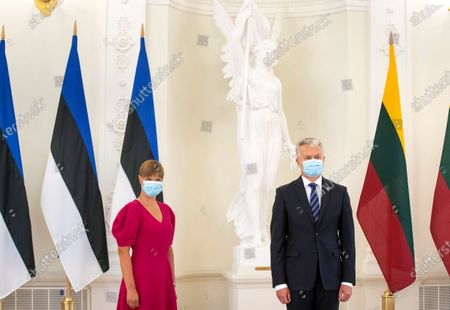 Lithuania's President Gitanas Nauseda, right, and Estonia's President Kersti Kaljulaid wearing a face masks to protect against the coronavirus, pose for photographers prior to their meeting at the Presidential palace in Vilnius, Lithuania