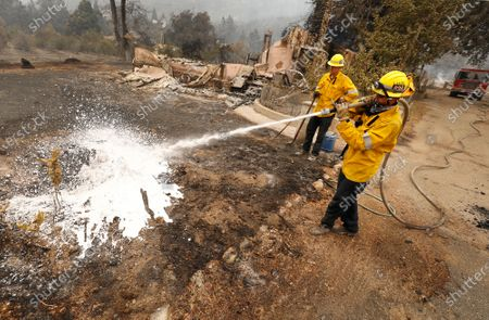 Los Angeles County Firefighter Brandon Smith, left, and Danny Natalizio, right, douse hot spots as several homes, out structures and other vehicles have been destroyed along Pine Canyon Road West of Lake Hughes after the out-of-control Lake Fire consumed over 10,000 acres yesterday promoting mandatory evacuations with 0% containment. Angeles National Forest on Thursday, Aug. 13, 2020 in Lake Hughes, CA. (Al Seib / Los Angeles Times)