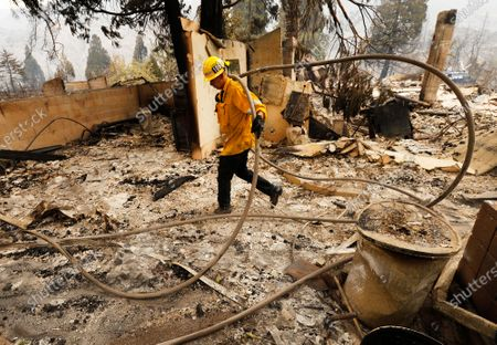 Los Angeles County Firefighter Brandon Smith runs hose through a burned out home to complete mop-up by dousing hot spots as several homes, out structures and other vehicles have been destroyed along Pine Canyon Road West of Lake Hughes after the out-of-control Lake Fire consumed over 10,000 acres yesterday promoting mandatory evacuations with 0% containment. Angeles National Forest on Thursday, Aug. 13, 2020 in Lake Hughes, CA. (Al Seib / Los Angeles Times)