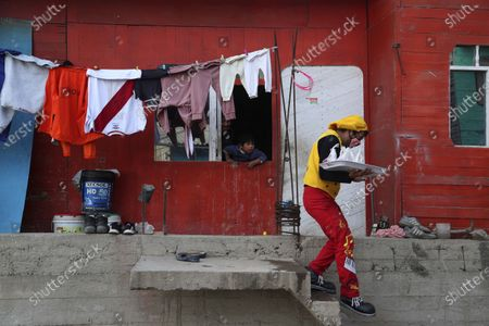 """Circus clown Julio Cesar Chiroque, 38, whose clown name is """"Galleta,"""" or Cookie, leaves a residence where he failed to sell candied apples as he makes the rounds in a poor neighborhood on the outskirts of Lima, Peru, . Chiroque's family used to run their own small circus, but since March when the lockdown to curb COVID-19 closed their business, and the requirement for seniors over 60 to self-quarantine kept his father home-bound, they started selling circus food to survive"""