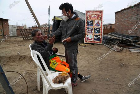 """Circus clown Julio Cesar Chiroque, whose performance name is """"Galleta',"""" or Cookie, right, helps put clown makeup on his father, Santos Chiroque, whose nickname is """"Piojito,"""" or Little Tick, outside their home in a poor neighborhood on the outskirts of Lima, Peru, . The Chiroque family used to run their own small circus, but since March when the lockdown to curb COVID-19 closed their business, and the requirement for people over 60 to self-quarantine kept the 74-year-old at home, they started selling circus food like caramelized apples to survive"""