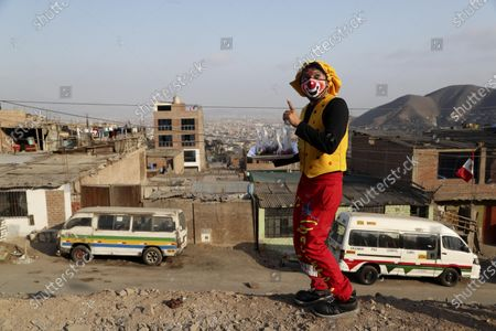 """Circus clown Julio Cesar Chiroque, 38, whose clown name is """"Galleta,"""" or Cookie, gestures to the camera as he canvases a neighborhood selling candied apples in a poor neighborhood on the outskirts of Lima, Peru, . Chiroque's family used to run their own small circus, but since March when the lockdown to curb COVID-19 closed their business, and the requirement for seniors over 60 to self-quarantine kept his father home-bound, they started selling circus food to survive"""
