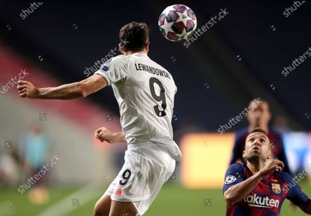 Barcelona's Jordi Alba, right, watches as Bayern's Robert Lewandowski leaps up for the ball during the Champions League quarterfinal match between FC Barcelona and Bayern Munich at the Luz stadium in Lisbon, Portugal