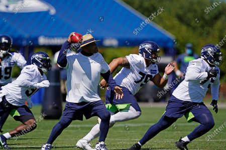 Seattle Seahawks defensive coordinator Ken Norton Jr. makes a passing motion as defensive end L.J. Collier, left, defensive tackles Bryan Mone, center, and Cedrick Lattimore right, run a practice drill during NFL football training camp, in Renton, Wash