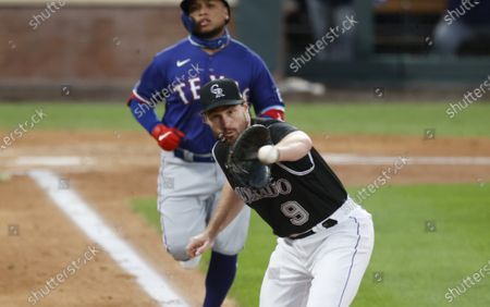 Colorado Rockies first baseman Daniel Murphy, front, fields the throw from second baseman Ryan McMahon to put out Texas Rangers' Willie Calhoun at first base in the fourth inning of a baseball game, in Denver