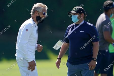 Seattle Seahawks head coach Pete Carroll, left, talks with general manager John Schneider during NFL football training camp, in Renton, Wash