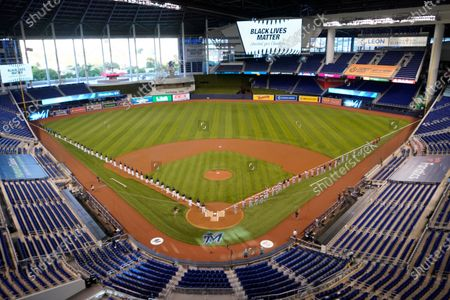 Miami Marlins players, left, and Atlanta Braves players, right, stand to honor Black Lives Matter before the start of a baseball game, in Miami Stok Görsel