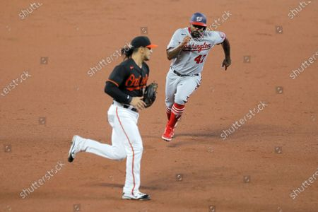 Washington Nationals' Howie Kendrick, right, runs the bases as Baltimore Orioles third baseman Rio Ruiz gets in position for the relay throw as Kendrick scores on a single by Carter Kieboom during the third inning of a baseball game, in Baltimore