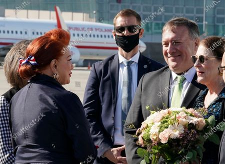 Secretary of State Mike Pompeo, second right, and his wife Susan talk with US Ambassador to Poland Georgette Mosbacher, left, as they arrive at the airport in Warsaw, Poland, . Pompeo is on a five day visit to central Europe