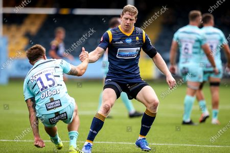 Scott van Breda of Worcester Warriors helps Jason Woodward of Gloucester Rugby to his feet