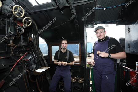Jack Colby (left) and Jamie Bond enjoy their breakfast of sausages and bacon, cooked on the coal shovel in the firebox of the 92 Squadron Battle of Britain steam locomotive as the Nene Valley Railway have resumed running steam trains from Wansford to Peterborough after the COVID-19 Coronavirus pandemic forced them to stop during lockdown.The 92 Squadron Battle of Britain 34081 steam train has been prepared and is ready to go, with the carriages having their capacity reduced to allow for new social distancing guidelines.