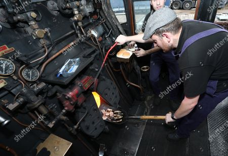 Paul Roe, left, and Jamie Bond cook sausages and bacon on the coal shovel, ready for the train team's breakfast, in the firebox of the 92 Squadron Battle of Britain steam locomotive as the Nene Valley Railway have resumed running steam trains from Wansford to Peterborough after the COVID-19 Coronavirus pandemic forced them to stop during lockdown.The 92 Squadron Battle of Britain 34081 steam train has been prepared and is ready to go, with the carriages having their capacity reduced to allow for new social distancing guidelines.
