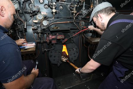 Stock Image of Paul Roe, left, and Jamie Bond cook sausages and bacon on the coal shovel, ready for the train team's breakfast, in the firebox of the 92 Squadron Battle of Britain steam locomotive as the Nene Valley Railway have resumed running steam trains from Wansford to Peterborough after the COVID-19 Coronavirus pandemic forced them to stop during lockdown.The 92 Squadron Battle of Britain 34081 steam train has been prepared and is ready to go, with the carriages having their capacity reduced to allow for new social distancing guidelines.