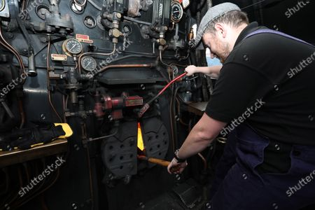 Jamie Bond has sausages and bacon on the coal shovel, cooking the train team's breakfast in the firebox of the 92 Squadron Battle of Britain steam locomotive as the Nene Valley Railway have resumed running steam trains from Wansford to Peterborough after the COVID-19 Coronavirus pandemic forced them to stop during lockdown.The 92 Squadron Battle of Britain 34081 steam train has been prepared and is ready to go, with the carriages having their capacity reduced to allow for new social distancing guidelines.