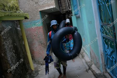 """Jean Carlos Almeida, 35, and Eric Mendez, 40, return home after a day of open sea fishing on their inner tubes, at Playa Escondida in La Guaira, Venezuela, amid the new coronavirus pandemic. """"If we had steady work, we wouldn't risk our lives out there,"""" said Almeida, who is accompanied by his fishing partner Mendez. """"We're bricklayers, but there's no construction"""