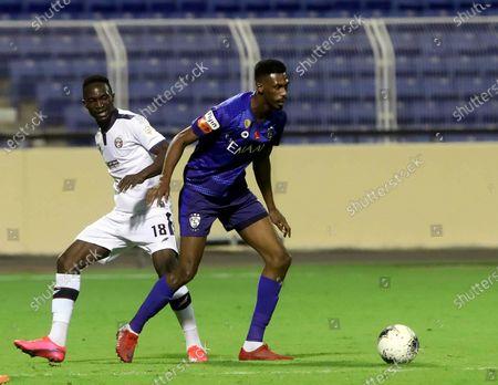 Al-Hilal's player Mohamed Kanno (R) in action against Al-Adalah's Adama Traore (L) during the Saudi Professional League soccer match between Al-Adalah and Al-Hilal, in Al-Hasa, Saudi Arabia, 15 August 2020.