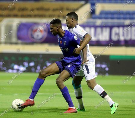 Al-Hilal's player Mohamed Kanno (L) in action against Al-Adalah's Bader Al-Nakhli (R) during the Saudi Professional League soccer match between Al-Adalah and Al-Hilal, in Al-Hasa, Saudi Arabia, 15 August 2020.