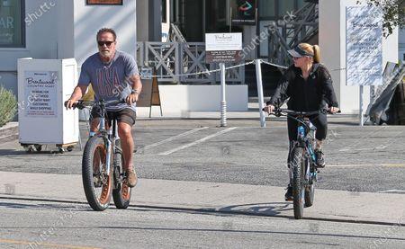 Arnold Schwarzenegger seen riding his bike in Brentwood with girlfriend Heather Milligan