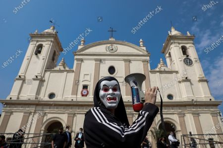 A man protests with a megaphone during a demonstration at the Metropolitan Cathedral of Asuncion, Paraguay, 15 August 2020. Former President Horacio Cartes (2013-2018) was rebuked with allegations of corruption by a group of people at the entrance of the Cathedral of Asuncion when he arrived to his daughter Sol Cartes' wedding with the businessman Patrick Bendlin.