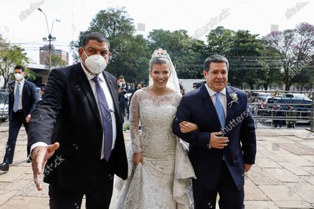 Sol Cartes (C) accompanied by her father, former Paraguayan President Horacio Cartes (R), arrives for her marriage to businessman Patrick Bendlin, at the Metropolitan Cathedral of Asuncion, Paraguay, 15 August 2020. Former President Horacio Cartes (2013-2018) was rebuked with allegations of corruption by a group of people at the entrance of the Cathedral of Asuncion when he arrived to his daughter Sol Cartes' wedding with the businessman Patrick Bendlin.