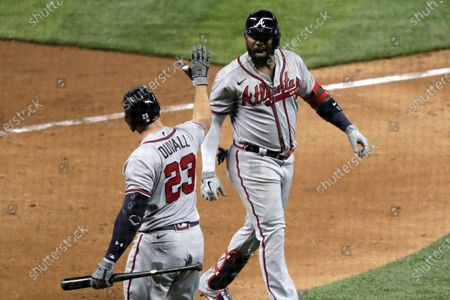 Atlanta Braves' Marcell Ozuna, right, is met by Adam Duvall (23) after scoring on a solo home run during the seventh inning of the team's baseball game against the Miami Marlins, in Miami