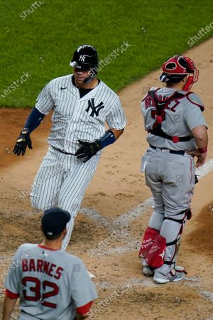 Stock Image of New York Yankees' Gary Sanchez runs past Boston Red Sox catcher Christian Vazquez, right, and relief pitcher Matt Barnes, left, to score on a sacrifice fly ball by Brett Gardner during the seventh inning of a baseball game, in New York