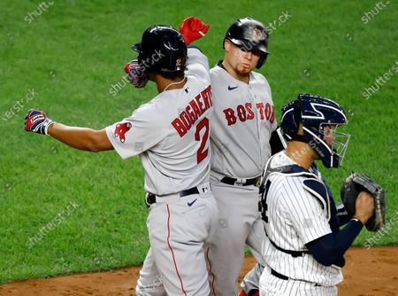 Boston Red Sox shortstop Xander Bogaerts (L) celebrates his solo home run with teammate Boston Red Sox catcher Christian Vazquez (C) off of New York Yankees starting pitcher James Paxton (not pictured) in the fourth inning during a MLB game at Yankee Stadium in the Bronx, New York, USA, 15 August 2020.