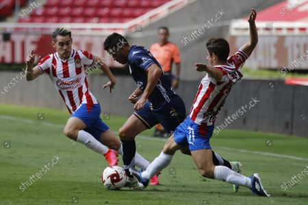 Stock Image of Chivas' Jesus Angulo (L) and Isaac Brizuela (L) in action against San Luis' Pablo Barrera (C) during a Guardianes 2020 day five match held at the Akron stadium in Guadalajara, Jalisco state, Mexico, 15 August 2020.