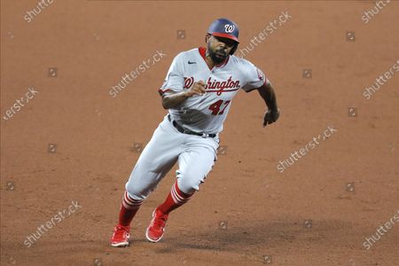 Washington Nationals' Howie Kendrick runs to third base before scoring a run against the Baltimore Orioles during the fourth inning of a baseball game, in Baltimore