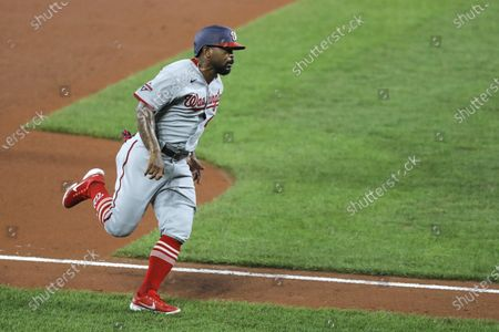 Washington Nationals' Howie Kendrick runs to home plate before scoring a run against the Baltimore Orioles during the fourth inning of a baseball game, in Baltimore