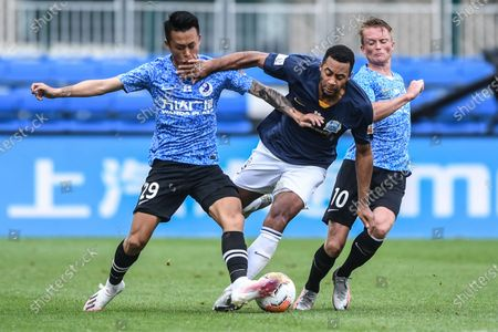 Mousa Dembele (C) of Guangzhou R&F vies with Sun Bo (L) of Dalian Yifang during the fifth round match between Guangzhou R&F and Dalian Yifang at the postponed 2020 season Chinese Football Association Super League (CSL) Dalian Division in Dalian, northeast China's Liaoning Province, Aug. 16, 2020.