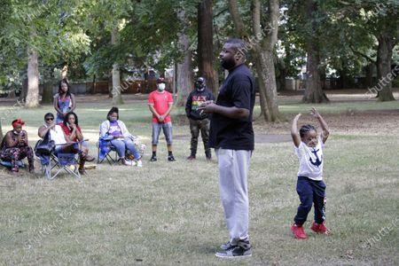 Sam Thompson, founder of Black Men and Women United, speaks to members of the Black community during a weekly meeting as his 3-year-old son, Jet, plays behind him in Portland, Ore., on . Thompson founded the group amid the ongoing protests in Portland with the goal of bringing long-term resilience to the city's Black community, which has endured years of racism