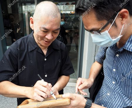 Taiwan-based Malaysian film director Tsai Ming-liang (L) signs an autograph for a fan in Taipei, Taiwan, 16 August 2020. According to news report, Tsai's film 'Days' is among the 25 feature films from 19 countries to be shown during the 2020 New York Film Festival which is scheduled to open on 17 September. 'Days' portrays the short romantic encourter of two men - Kang, played by Taiwanese actor Lee Kang-sheng, and Non, played by Laotian immigrant Anong Houngheuangsy - in Bangkok, Thailand.