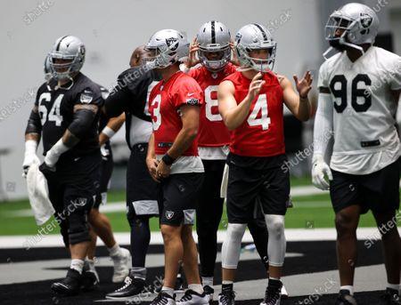 Las Vegas Raiders quarterbacks Nathan Peterman (3), Marcus Mariota (8) and Derek Carr (4) gather during an NFL football training camp practice, in Henderson, Nev