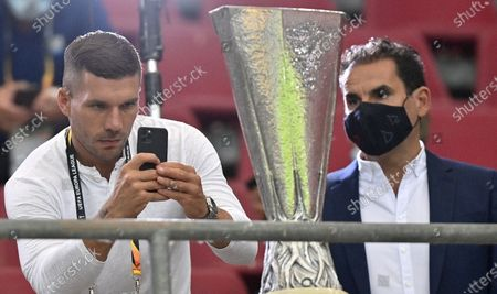 Stock Image of German soccer player Lukas Podolski (L) takes a photo of the trophy prior to the UEFA Europa League semi final match between Sevilla FC and Manchester United in Cologne, Germany, 16 August 2020.