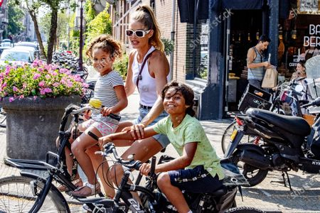 Stock Picture of Doutzen Kroes shops and rides bikes with her chidren, Myllena Gorre and Phyllon Gorre