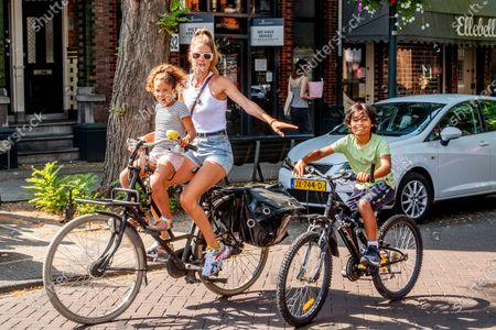 Stock Image of Doutzen Kroes shops and rides bikes with her chidren, Myllena Gorre and Phyllon Gorre