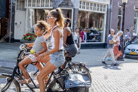 Stock Photo of Doutzen Kroes shops and rides bikes with her chidren, Myllena Gorre and Phyllon Gorre