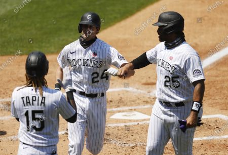 Colorado Rockies' Ryan McMahon, center, is congratulated by teammates Raimel Tapia, left, and Matt Kemp as he crosses home plate after hitting a three-run home run off Texas Rangers starting pitcher Kolby Allard in the second inning of a baseball game, in Denver