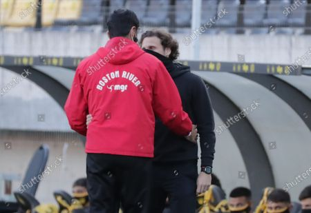 Head coach of Penarol, former Uruguayan soccer player Diego Forlan (R), greets his Boston River counterpart, former Uruguayan soccer player Sebastian Abreu, during the Apertura tournament soccer match between Club Atletico Penarol and Club Atletico Boston River at Campeon del Siglo stadium in Montevideo, Uruguay, 16 August 2020.