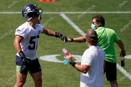 Seattle Seahawks general manager John Schneider, right, bumps fists with linebacker Cody Barton, during an NFL football training camp in Renton, Wash