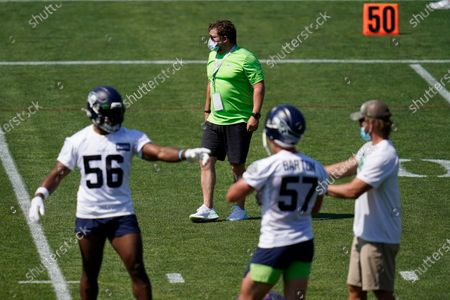 Seattle Seahawks general manager John Schneider, center back, looks, during an NFL football training camp in Renton, Wash