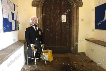 A scarecrow of Sir Colonel Tom Moore in the entrance to the All Saints Paston church in Peterborough. Because of the COVID-19 Coronavirus pandemic, the Werrington Show is not able to go ahead in the normal manner, but they have still organised a scarecrow trail with an effigy of Sir Colonel Tom Moore being one of the 29 scarecrows.To avoid people touching the scarecrow, it is currently behind the bars on the entrance to the church, which is also closed, but will be open on Sunday, and the Werrington Show Scarecrow Trail is on over the weekend on Saturday and Sunday August 15 and 16.