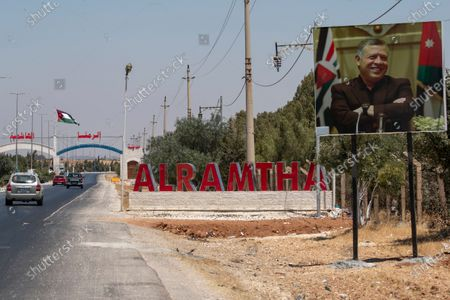 A poster depicting King Abdullah II of Jordan is seen over the entrance of the recently locked down town of al-Ramtha, some 70 km north of Amman, near the Jordanian Syrian border, Jordan, 17 August 2020. Due to a hike in the numbers of local COVID-19 Coronavirus cases in the past week to 122 cases, Jordan has closed its land border crossings  for one week. The town of al-Ramtha near Irbid where many of the local cases emerged, was put in isolation on 16 August. The Jordanian government announced on 17 August, 20 new cases, 16 of them local and four others at quarantine hotels.