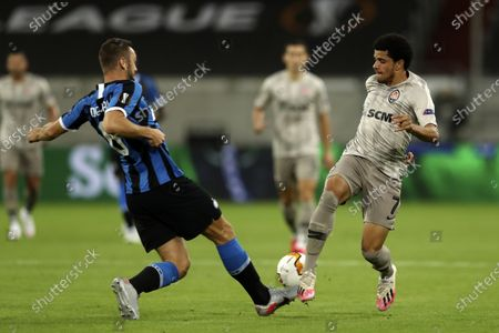 Inter Milan's Stefan de Vrij, left, and Shakhtar's Taison fight for the ball during the Europa League semifinal soccer match between Inter Milan and Shakhtar Donetsk at Dusseldorf Arena, in Duesseldorf, Germany