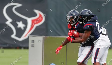 Houston Texans running backs David Johnson, left, and Duke Johnson (25) run a ball control drill during an NFL training camp football practice, in Houston