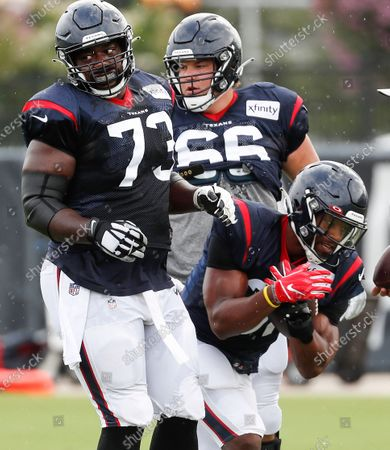 Houston Texans running back David Johnson (31) runs the ball between guard Zach Fulton (73) and center Nick Martin (66) during an NFL training camp football practice, in Houston